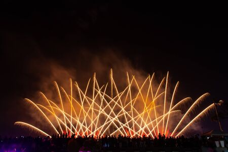 Photo for Crowd looks holiday fireworks in dark evening sky. - Royalty Free Image