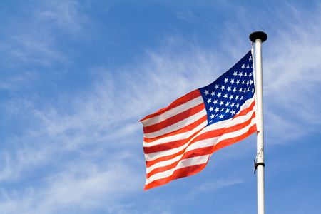 Waving american flag on blue sky background
