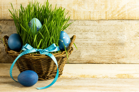 blue easter eggs in a basket, with grass, over wooden backgroundの写真素材
