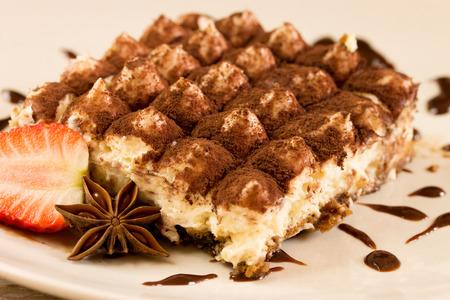 Photo pour tiramisu cream dessert on a plate with strawberry and Anisse - image libre de droit