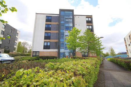 Photo pour view of block of flats with walkway and hedges in view. - image libre de droit