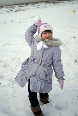 Young girl is throwing snowball in winter
