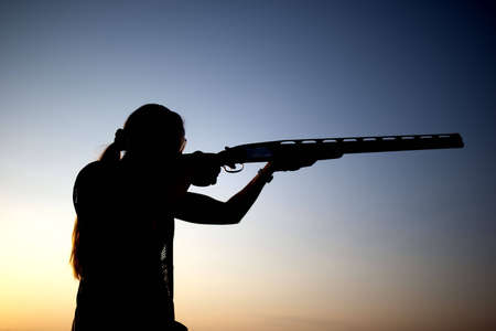 Woman shoots with his gun silhouette