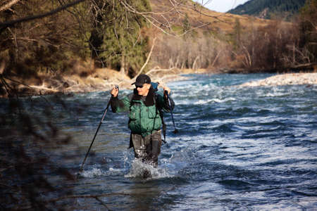 Backpacker wade rugged mountain river