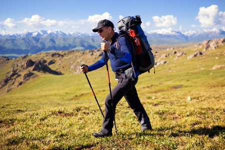 Hiker in mountains at grassland with sky