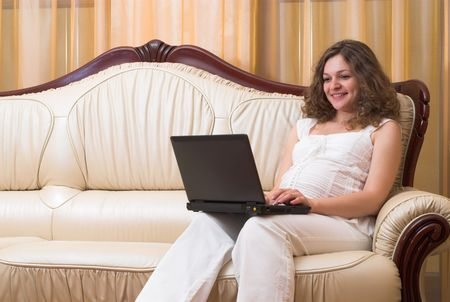 Young pregnant woman is sitting in sofa with laptop