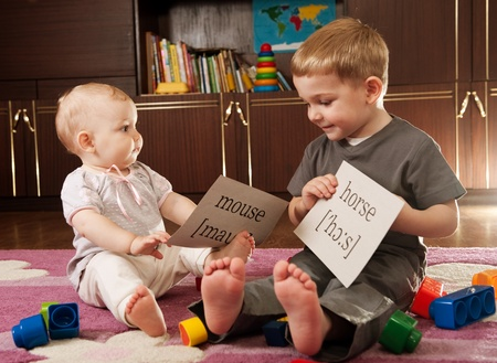 A boy aged three and a girl aged one are playing with blocks and cards with words