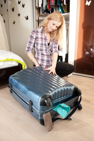 Young blonde pregnant woman packing travel bag at homeの写真素材
