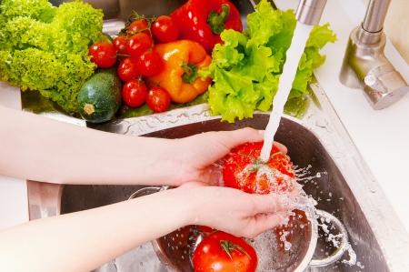 Photo pour Fresh vegetables under water stream in colander - image libre de droit