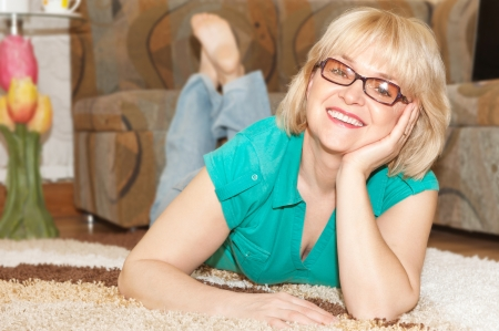 Blonde woman with toothy smile lying on floor at home