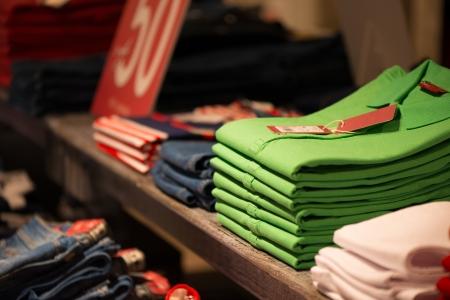 Foto de Various colour shirts at shelf in shop  - Imagen libre de derechos