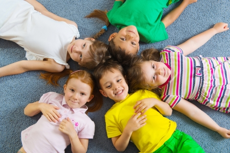 Cute little children lying on floor in kindergarten