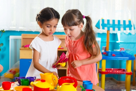 Two cute little girls playing role game in daycare