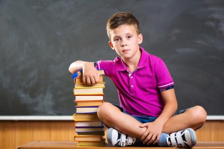 Cute school boy sitting with books against blackboard in classroom