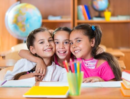 Photo pour Portrait of smart schoolchildren looking at camera in classroom - image libre de droit