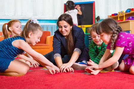 Children with tutor plaing development games at kindergarten
