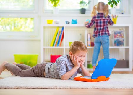 Photo pour Little intelligent boy play with toy laptop at home - image libre de droit