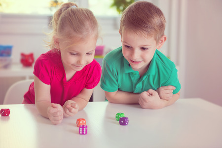 Two happy children playing with dices at home