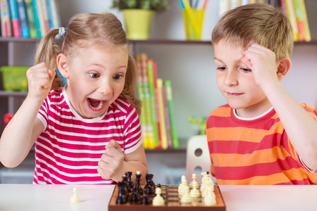 Photo for Two cute children playing chess at home - Royalty Free Image