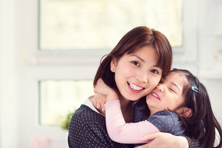 Photo pour Portrait of happy japanese mother hugging with her cute little daughter at home - image libre de droit