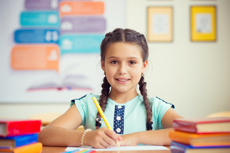 Foto de Cute smiling schoolgirl at school during lesson - Imagen libre de derechos