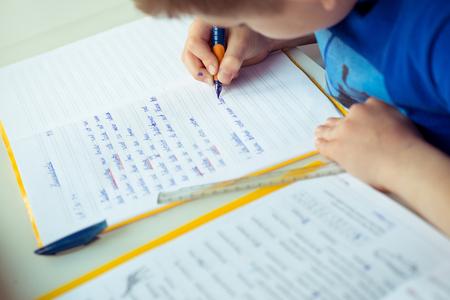 Photo pour Intelligent boy makes homework at desk in his room - image libre de droit