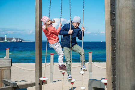Photo pour Two happy children playing at playground on a beach - image libre de droit