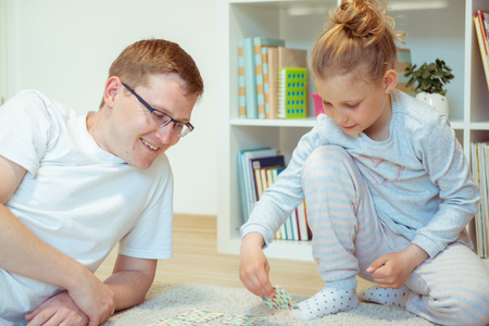 Photo pour Happy young father playing with his cute little daughter in bright room at home - image libre de droit