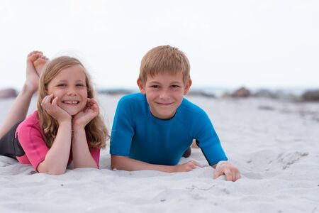 Photo pour Portrait of two happy children in neoprene swimsuits playing on the beach with sand on Baltic sea - image libre de droit