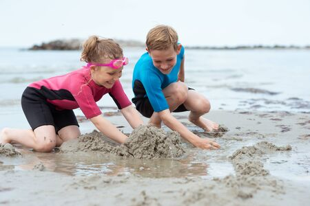 Photo pour Two happy siblings children in neoprene swimsuits playing with sand in a Baltic sea - image libre de droit