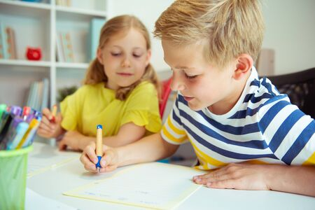 Photo pour Cute schoolchildren are came back to school and learning and writing  at the table in classroom - image libre de droit