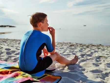 Photo pour Portrait of handsome teen boy in neoprene swimsuit in Baltic sea - image libre de droit