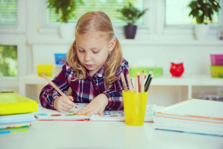 Photo pour Portrait of pretty school girl in yellow are studying at classroom at the table - image libre de droit