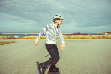 Photo pour Happy teenager boy in helmet, inline skates and safety equipment is happy learning skating sunny day in summer - image libre de droit