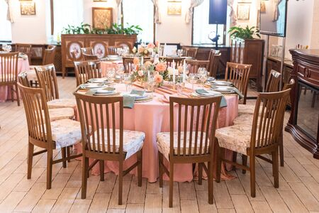 Photo pour Elegant festive banquet decoration in peach and green colors. Candles and bouquets of fresh flowers at the round tables - image libre de droit