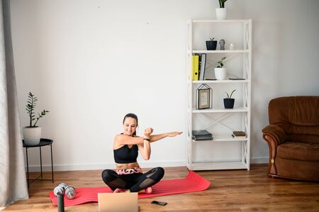 Foto de Stay home. Workout video tutorial. A young girl does exercises and looks at the screen of a laptop. Concept of online learning, full at home workout video - Imagen libre de derechos
