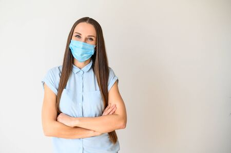 Photo pour Safety during a pandemic, epidemic, seasonal flu. Positive young woman in medical mask on her face standing with arms crossed on her chest - image libre de droit