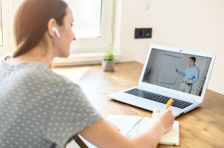 Photo for A man is online tutor, teacher with flip chart on the laptop screen, a young woman student is watching and writing. Back view. Online education, online learning - Royalty Free Image