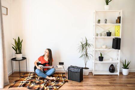 Photo pour A girl spends home leisure playing an electric guitar. Hobby concept, talent - image libre de droit