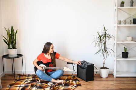 Photo pour A young woman spends home leisure at quarantine with playing an electric guitar, she sits on a plaid on the floor and sets up a combo amp - image libre de droit
