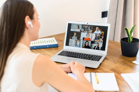Foto de Virtual video conference, online meeting with a many employees together. A young woman is communicating via video call with coworkers, a several webcam shot of people on the laptop screen - Imagen libre de derechos