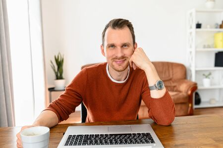 Photo pour Webcam view of attractive guy, he sits at the table with a cup of coffee, looks at camera and smiles. Video chat, video call, zoom - image libre de droit