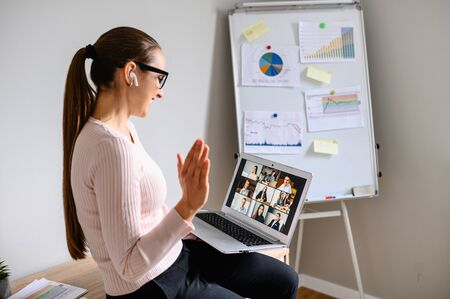 Photo for Morning meeting online. A young woman is using app on laptop for connection with colleagues, employees. Video call with many people together. Back view - Royalty Free Image