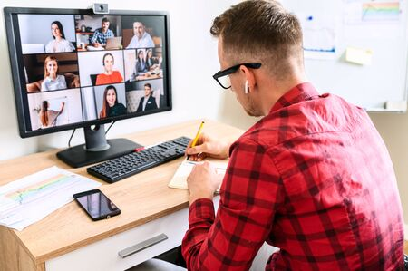 Foto de A young busy guy is making notes at the online conference video call with colleagues. He sits at the office desk, you can see his interlocutors on the PC screen - Imagen libre de derechos