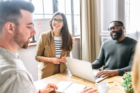 Photo pour A friendly atmosphere in the office. Young, confident employees of the multiracial team discuss tasks and laugh at the morning meeting - image libre de droit