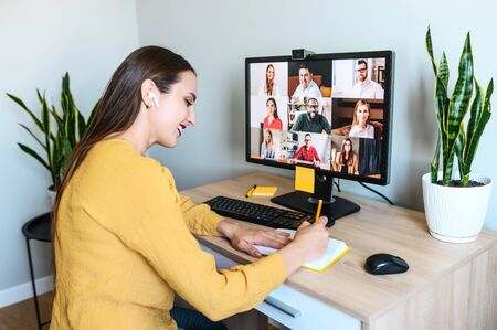 Photo for Virtual conference, morning meeting online. A young woman is using app on pc for connection with colleagues, employees, she is writing in notebook. Video call with many multiracial people togethe - Royalty Free Image