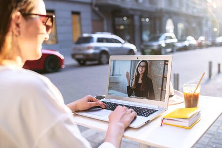 Photo for Virtual meeting with a friend. Young woman sits at the table in the street cafe and uses laptop for video call to another woman, two female friends are talking online - Royalty Free Image