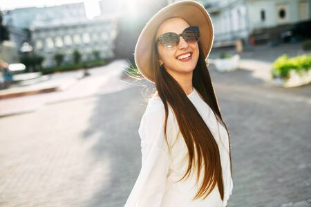 Foto de Cheerful beautiful brunette in a stylish hat and sunglasses looks at the camera and laughs happily. Stylish young woman with long hair walks around the city - Imagen libre de derechos