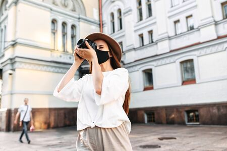 Photo pour Tourism after quarantine. Young girl tourist in a protective medical mask walks around the city and photographs the sights - image libre de droit