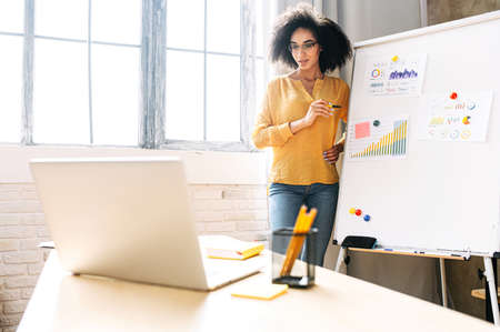 Photo pour Dark skinned young woman is conducts online webinars, online classes, online presentation. African girl explains something on a flip-chart in a office classroom to virtual audience on a laptop - image libre de droit